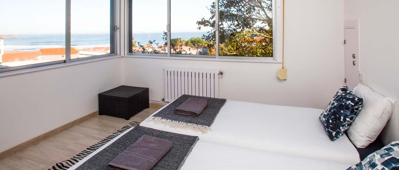 Meerblick-Suite mit Betten im Vordergrund und Blick auf den Strand und das Meer durch die Fenster