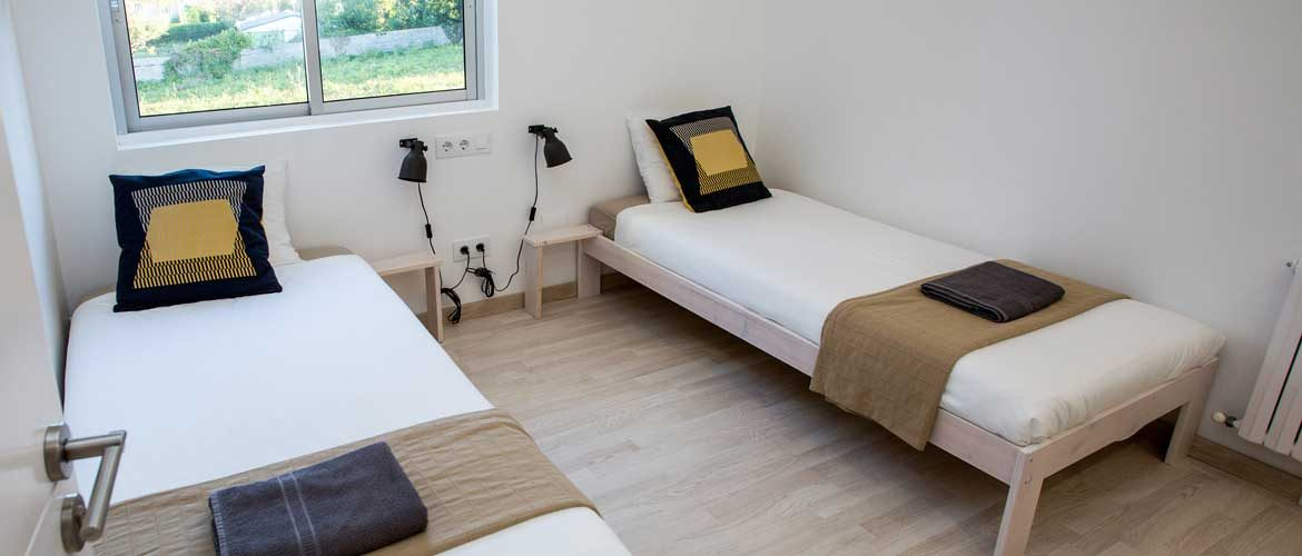 On of Casa Mamut's twin rooms with two individual beds and a window to the garden
